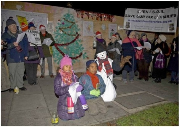 Community singing carols at the Wall of Shame
